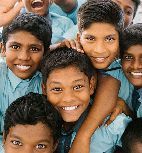 a group photo of smiling Indian schoolchildren waving