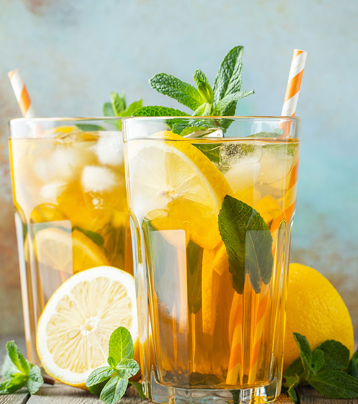 fresh iced tea in a tall glass with lemon and mint
