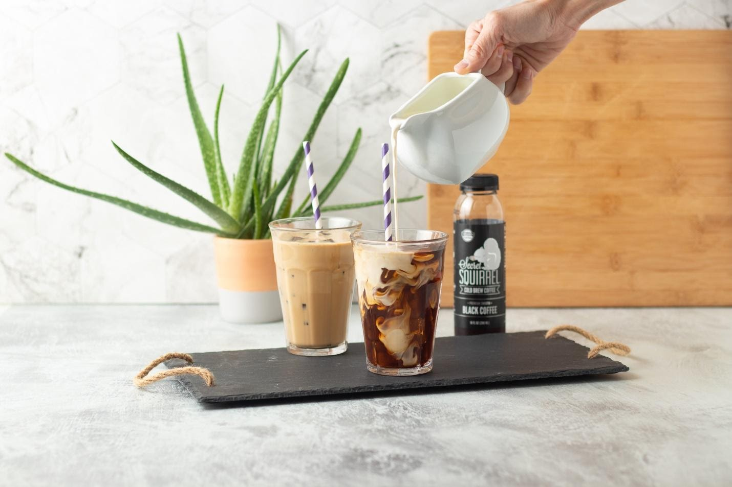 pouring milk in glass of Secret Squirrel cold brew coffee with bottle in the background