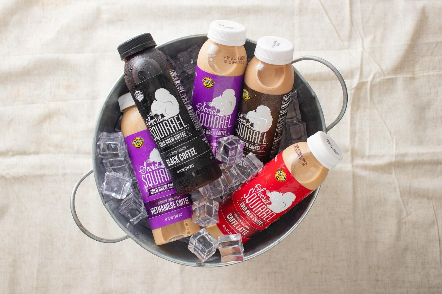 five bottles of Secret Squirrel cold brew coffee in a bucket filled with ice