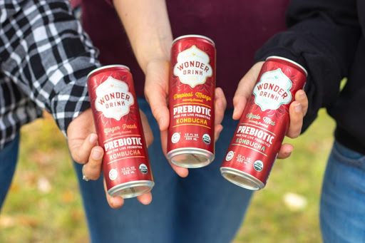 holding out three cans of Wonder Drink prebiotic Kombucha in ginger peach, tropical mango and apple mint flavors