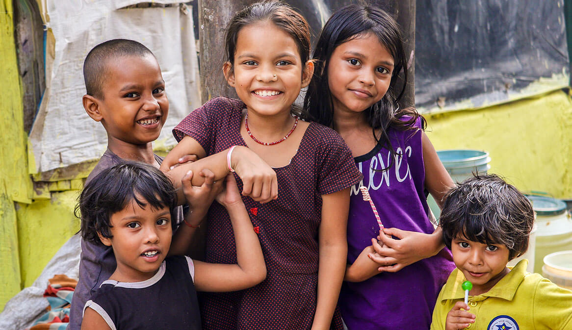 happy children in the streets of India holding hands and smiling