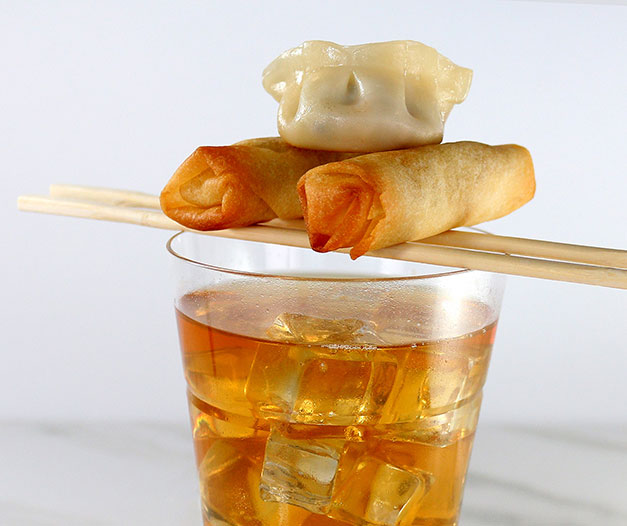 decorated food pairing of iced tea and spring rolls and dumpling on chopsticks