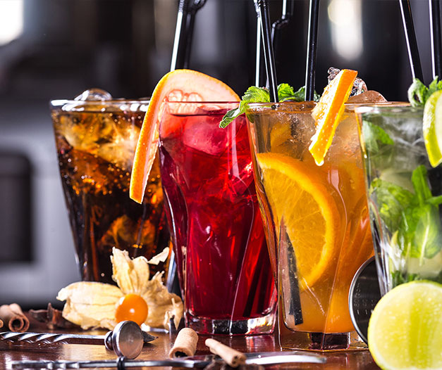 variety of iced tea with various garnishes on table