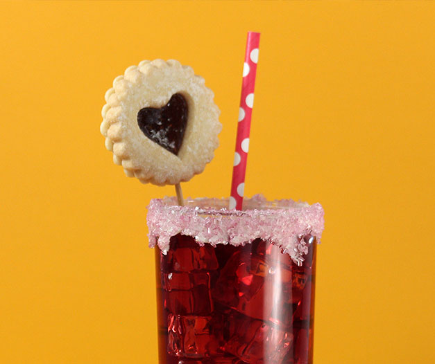 iced tea in sugar frosted highball glass with straw and pastry garnish