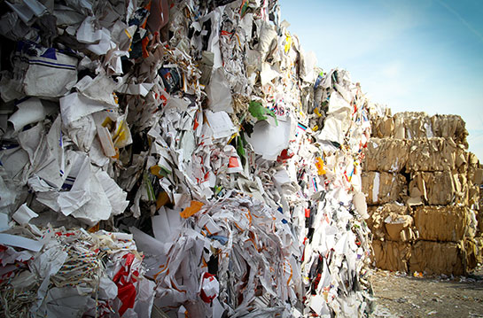 stack of trash and recyclable materials in a landfill